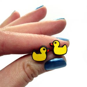 hand holding little yellow rubber duck shaped stud earrings